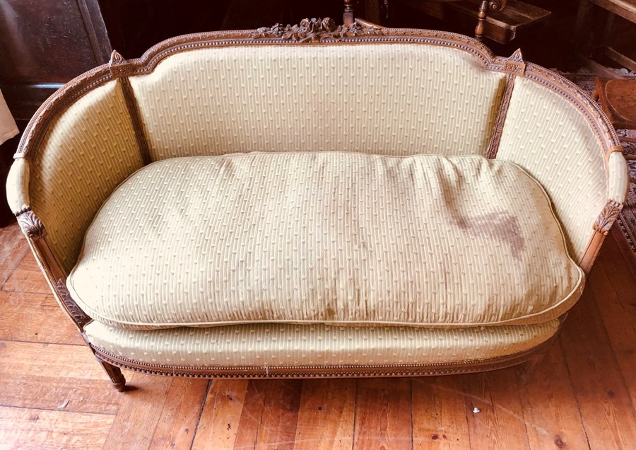 Lot 3032 - A 19th Century French Empire style walnut carved sofa, curved scroll arms, raised on turned tapering