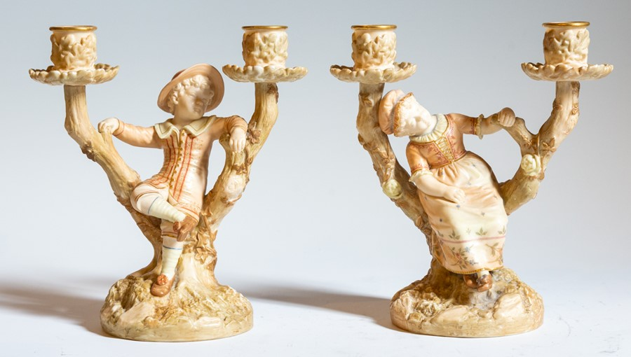 Lot 2432 - A pair of Royal Worcester blush ivory boy and girl candlesticks, both signed Hadley, each