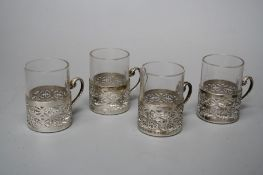 A set of four silver framed early 20th century Turkish coffee glasses. The frames with scroll handle