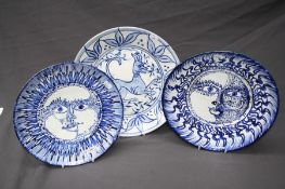 A Picasso- esque blue and white Spanish pottery plate painted with a radiant sun head design in coba