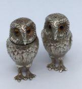 A pair of Elizabeth II silver pepperettes, realistically cast as owls, glass eyes, Garrard & Co,