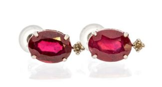 A pair of ruby and diamond 18ct white gold earrings, comprising faceted oval rubies claw set with