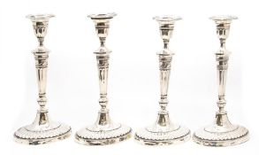 A set of four late Victorian silver candlesticks in the neo classical style, each with detachable