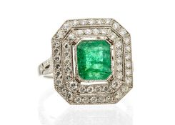 An emerald and diamond platinum ring, comprising an emerald cut emerald rub-over set to the