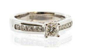 A diamond and 14ct white gold solitaire ring, the central claw set princess cut diamond weighing