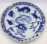 A Chinese blue and white charger decorated with prancing horses within river landscape with three