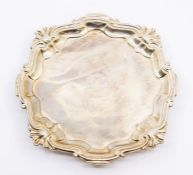 A George III silver plain salver with raised shell and wavy border, on three hoof feet, the centre