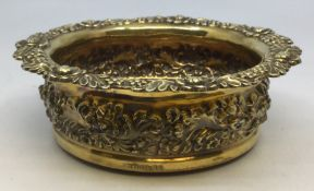 A George III silver wine coaster, repousse and chased with scrolls and flowers in central section,