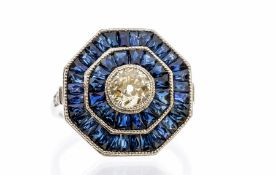 An Art Deco style sapphire and diamond platinum set cocktail ring, comprising a central rub-over set