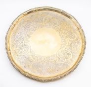 A George III silver salver, gadroon rim the centre engraved with a scrolling foliate, scale and