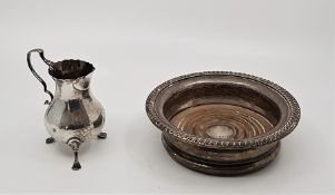 A silver coaster, by Ellis & Co, assayed London 1927, with gadrooned rim and turned wood base,