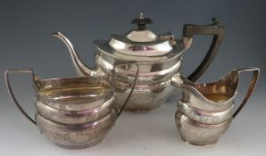 A Geo III style, matching but composite, three piece silver tea set with bright cut ogee body.