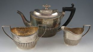 A late Geo III style matching but composite, three piece silver tea set with half reeded bodies.