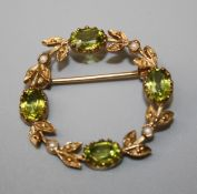 A gold peridot and seed pearl garland brooch set with four oval cut peridots and seed pearl set