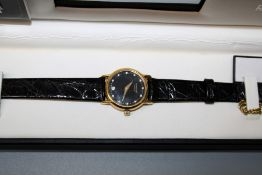 A gift boxed Raymond Weil of Geneva 18ct gold plated manual winf ladies watch with stone set black