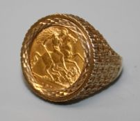 A 9ct textured ring rub over set half sovereign, dated 1915