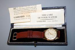 A 9ct gold Garrard gentleman's presentation wristwatch. Champagne Arabic dial with leather strap.
