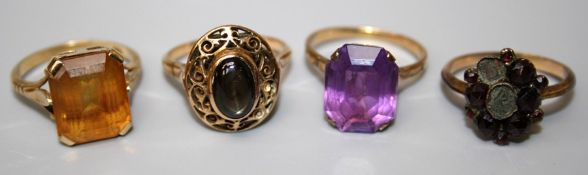 A single stone amethyst dress ring, a single stone citrine dress ring, a cats eye dress ring and a