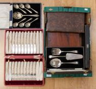 A box containing various cutlery sets, comprising cake knife and fork set, set of dessert spoons,