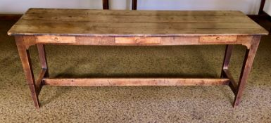 An early 20th Century oak farmhouse kitchen table, three planked top above three single frieze