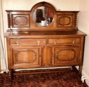 An early 20th Century oak Queen Anne revival sideboard, moulded pediment above a circular mirror