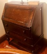 A mid 20th century oak fall front bureau, enclosing with fitted pigeon holes, above two drawers