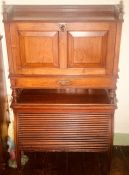 An early 20th century oak fall front bureau on tambour cupboard, three quarter gallery top above a