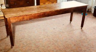 An early 20th century pine farmhouse kitchen table on later castors. 74cm H x 223cm L x 61cm W