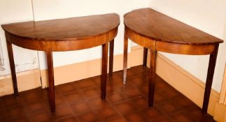 A pair of George III mahogany demi-lune tables, circa 1790, in Hepplewhite form, raised on tapered