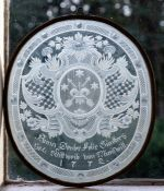 A late 18th Century German oval etched glass panel, scrollwork heraldic crest containing crossed
