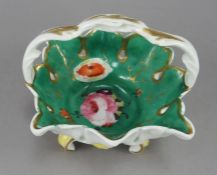 An early nineteenth century English porcelain handled and footed basket, c. 1820-30. It is hand-