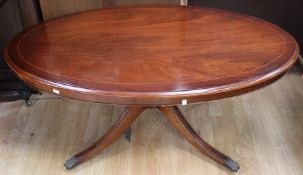 A contemporary mahogany effect oval pedestal coffee table, measuring 53cm high, 125cm wide, 71cm