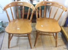LOCATED AT GRESLEY A pair of modern pine kitchen armchairs, in the style of captains chairs