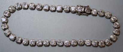 A diamond set line or tennis bracelet, the thirty eight stones mounted in white gold, stamped .750