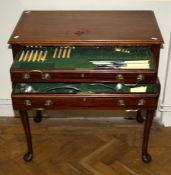 An Edwardian mahogany canteen table containing a twelve place setting of EPNS flatware and cutlery