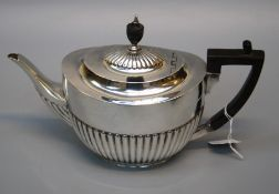 William Hutton and sons Ltd., an Edwardian silver teapot of demi gadrooned form with bakelite