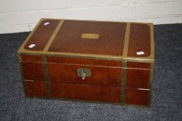 A Victorian amboyna and brass bound writing slope, the hinged top and front opening to reveal twin