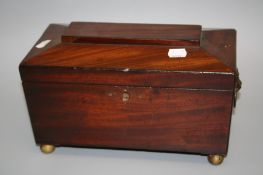 A 19th century mahogany sarcophagus form tea cannister with twin lidded caddy interior and