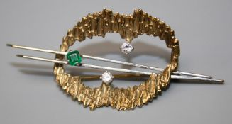 An emerald and diamond brooch, of open abstract form with a textured 9ct gold loop set with two