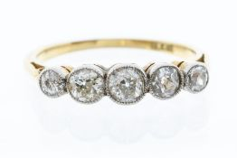 An Edwardian diamond and 18ct gold ring, comprising five graduated old cut diamonds with a total