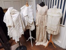 A wedding dress with a bustle in figured silk 1930s/40 and a child's dress in fine cotton with