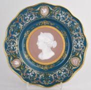 Prunkvoller Pâte-sur-Pâte-Teller Manufaktur Meissen, Schwerter unterglasurblau, I. Wahl, vertiefter Spiegel, die breite Fahne mit Wellenrand, Fond in Grünblau, im Spiegel Rundmedaillon in Rosé, darin in feiner Pâte-sur-Pâte-Malerei antikes Frauenbildnis im Profil, die Fahne mit barocker Blattornamentik und drei weiteren roséfarbenen Kartuschen ebenfalls in Pâte-sur-Pâte-Technik gestaltet, dazu feine Goldauflagen, in den Kartuschen die Musenattribute Aulos, Theatermaske, Triangel und Zim...
