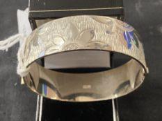 Hallmarked Silver: Hinged bangle with floral decoration hallmarked Birmingham. Weight 43·3g.