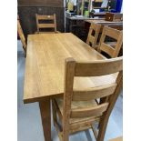 Good quality solid oak modern extending dining table with a set of matching four ladder back