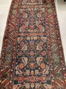 Carpets & Rugs: Late 19th cent. Persian wool runner with red ground, stylised flowers in blues,