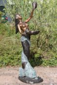 Mermaid on dolphin as a fountain figure, bronze, brown, golden brown and greenish patinated, water
