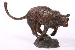 Wildcat, bronze, brown patinated and anthracite-colored spotted, with the prey at the start of the