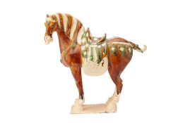 A CHINESE TANG STYLE SANCAI GLAZED MODEL OF A HORSE