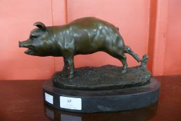 A bronze figure of a pig on a marble plinth