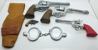 Three cap guns, Lone Star and Crescent Toys, a pair of toy handcuffs and a holster
